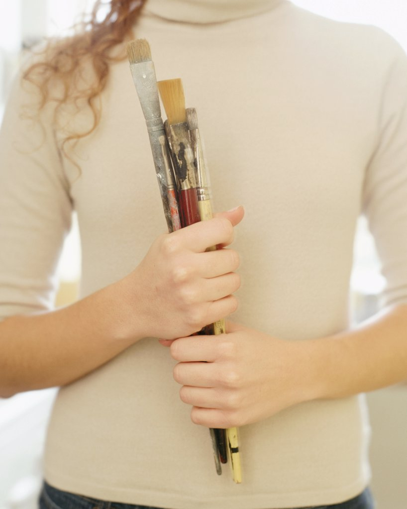 Woman holding paint brushes : Stock Photo
