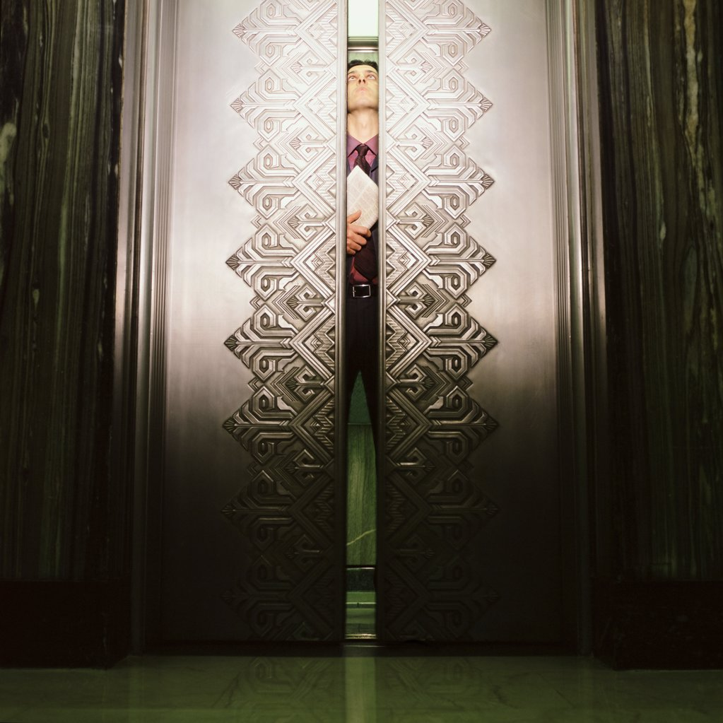 Man peering through elevator doors : Stock Photo
