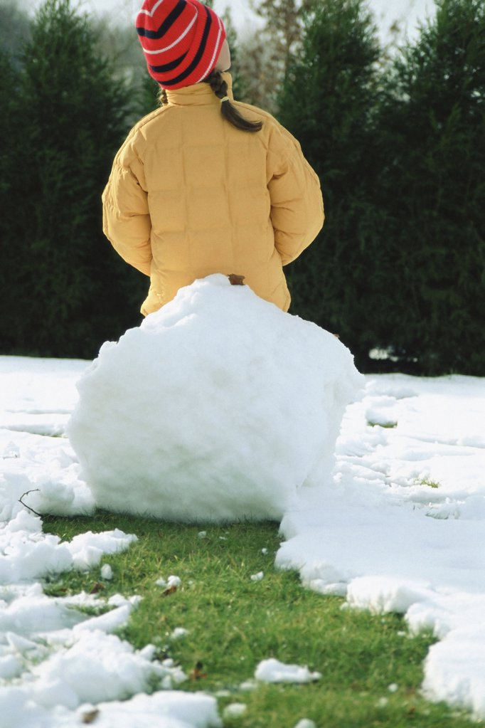 Stock Photo: 1439R-550094 Girl sitting on a big snowball
