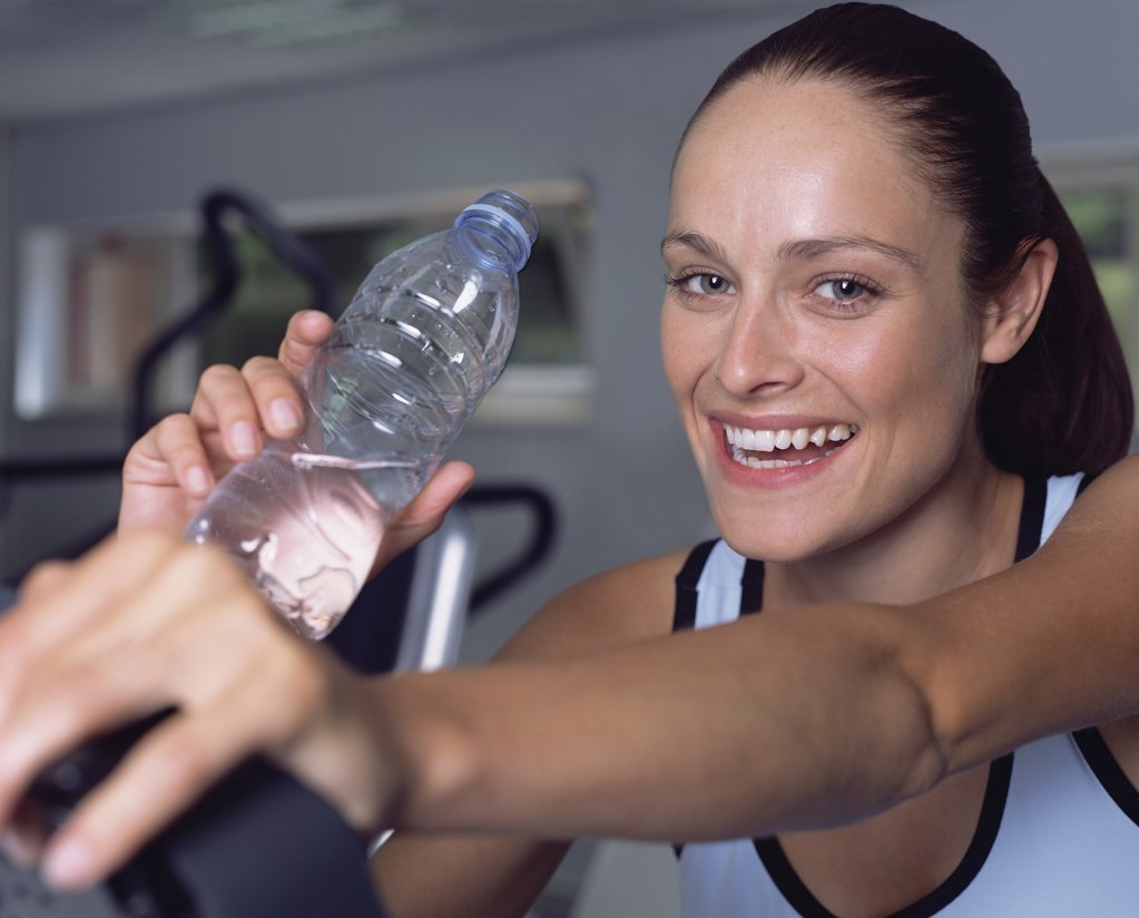 Woman drinking water in a gymnasium : Stock Photo