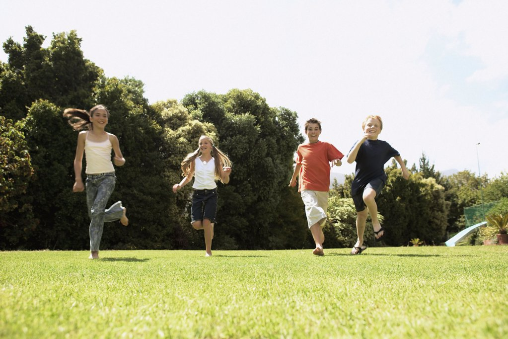 Children running on the grass : Stock Photo
