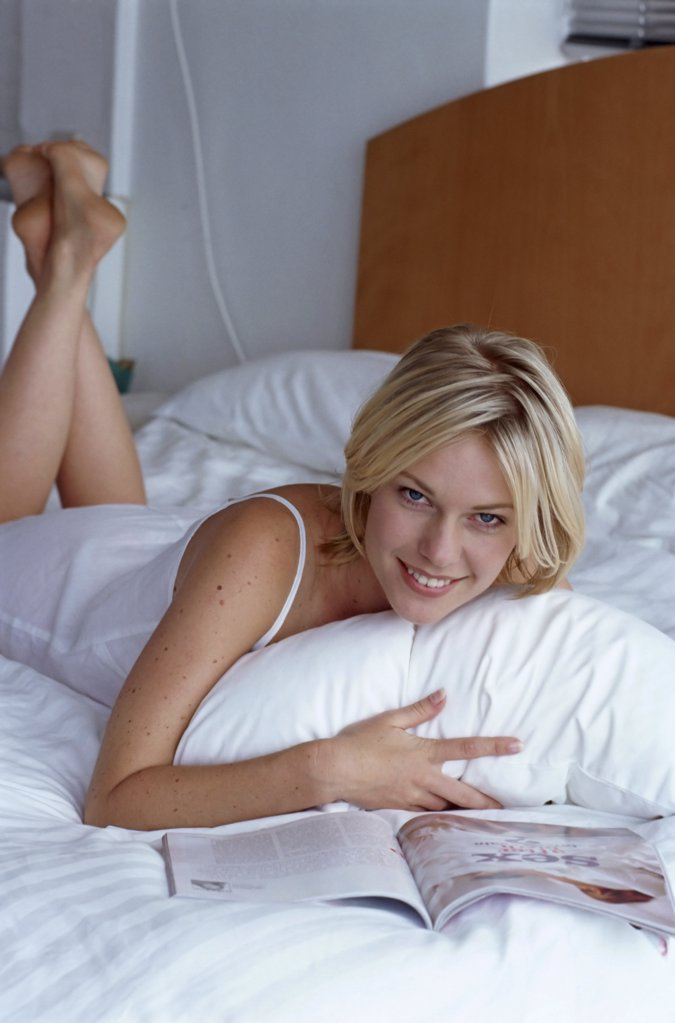 Stock Photo: 1439R-59009 Girl reading in bed