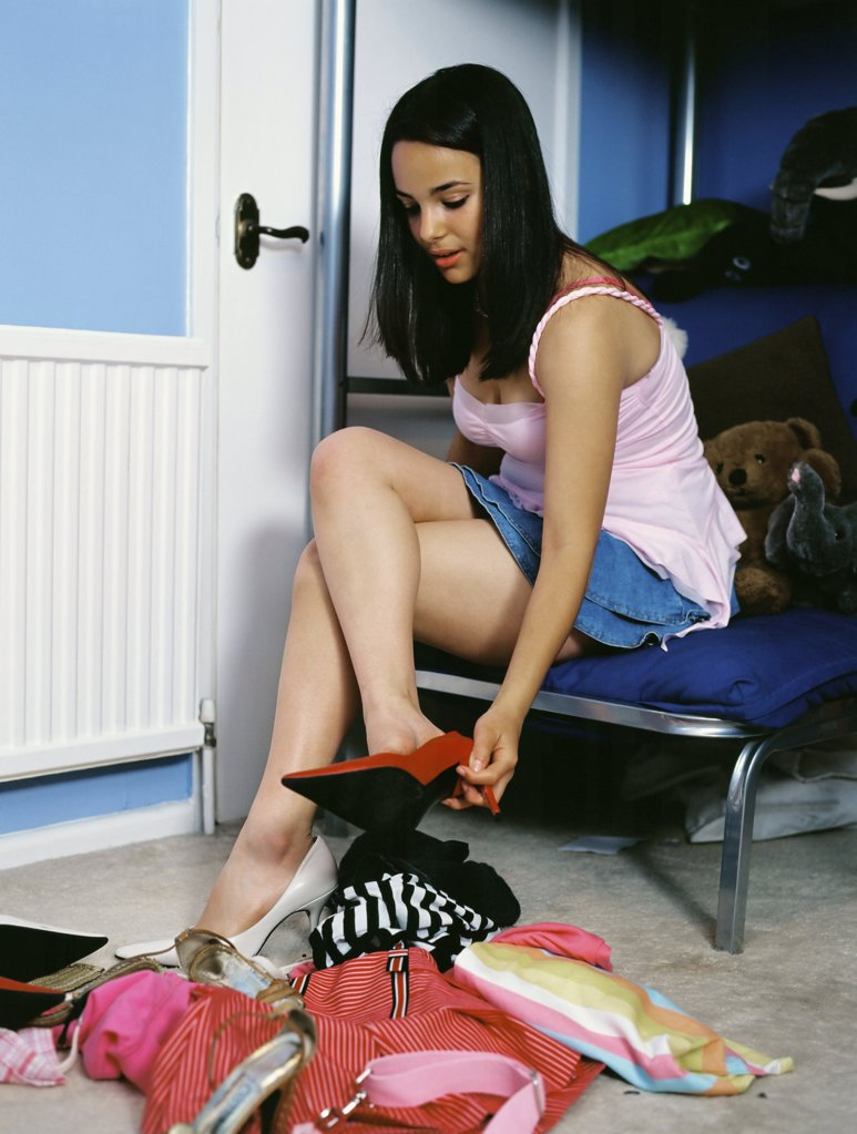 Girl trying on clothing in bedroom : Stock Photo