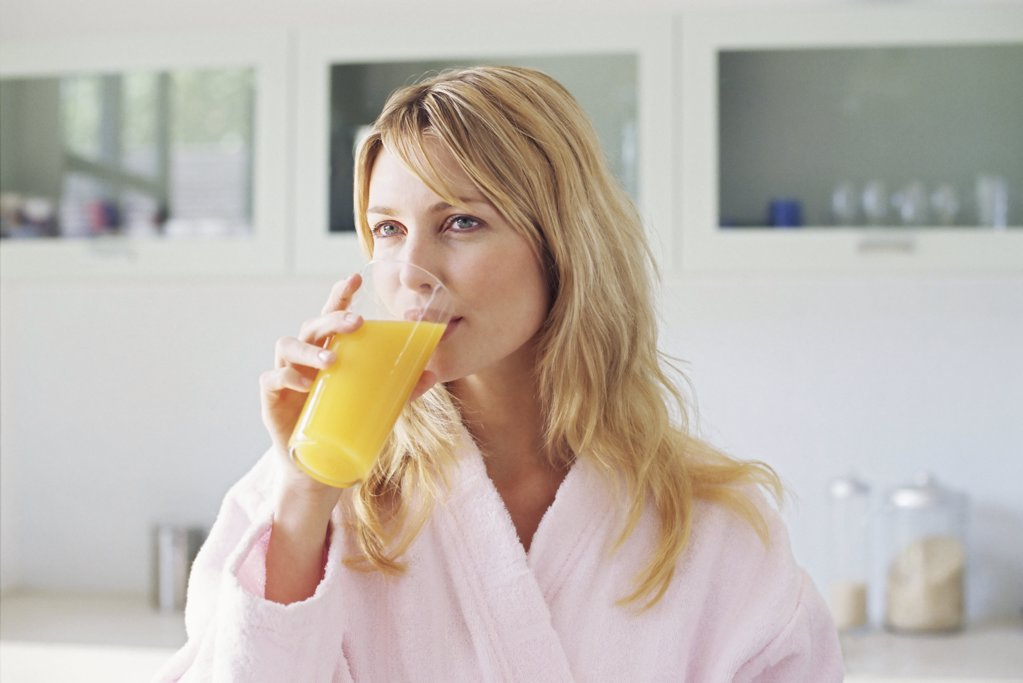 Stock Photo: 1439R-659020 Woman drinking orange juice