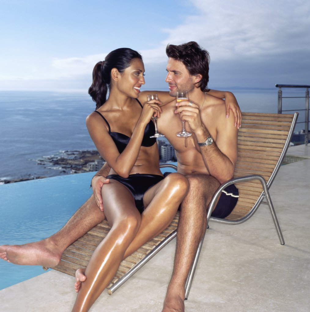Couple on a sunlounger with champagne : Stock Photo