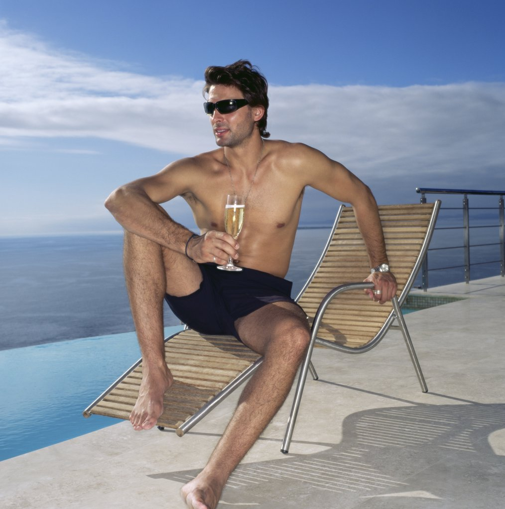 Stock Photo: 1439R-674043 Man on a sun lounger with champagne glass