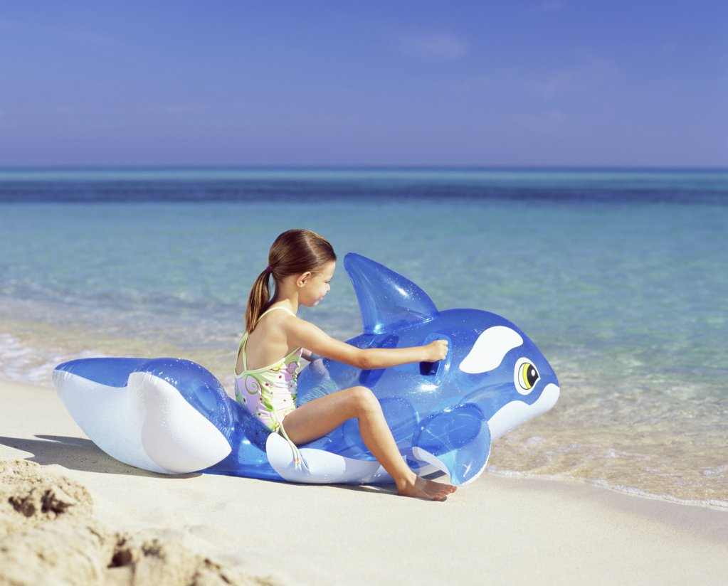 Stock Photo: 1439R-678073 Girl on inflatable whale