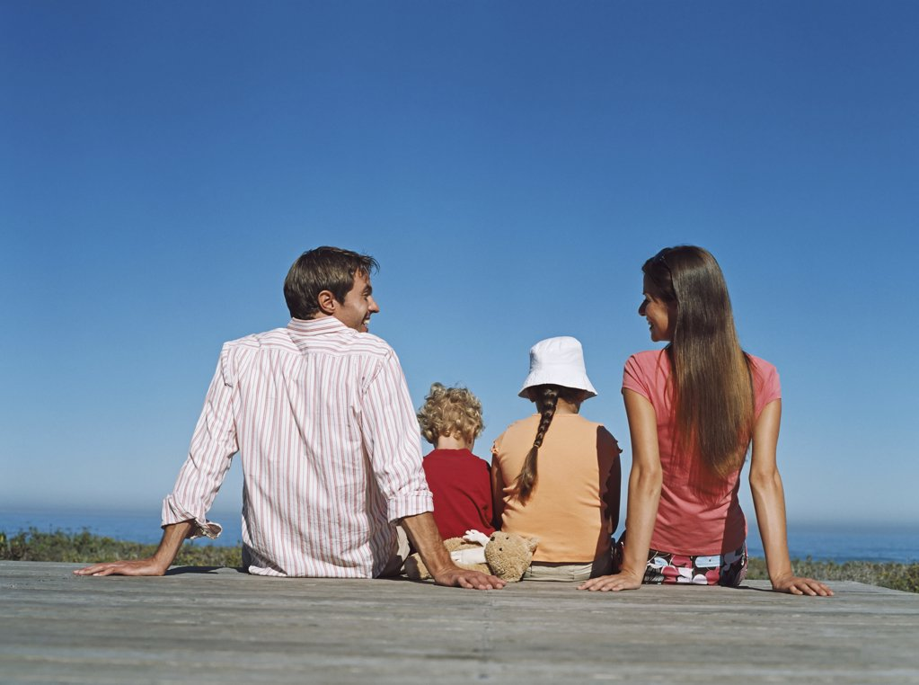 Stock Photo: 1439R-679031 Family sitting on a deck
