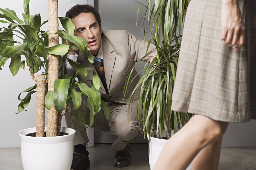 Stock Photo: 1439R-990065 Man hiding in plants and watching woman