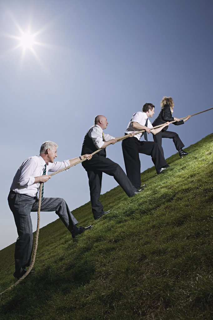 Business people climbing hill with rope : Stock Photo