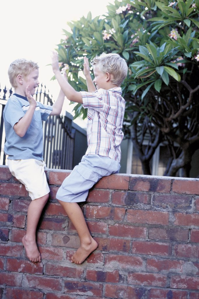 Boys playing on wall : Stock Photo