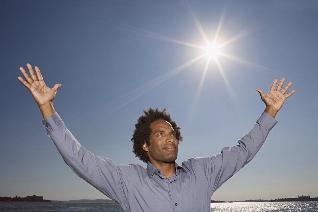 Man with his arms raised to the sky : Stock Photo