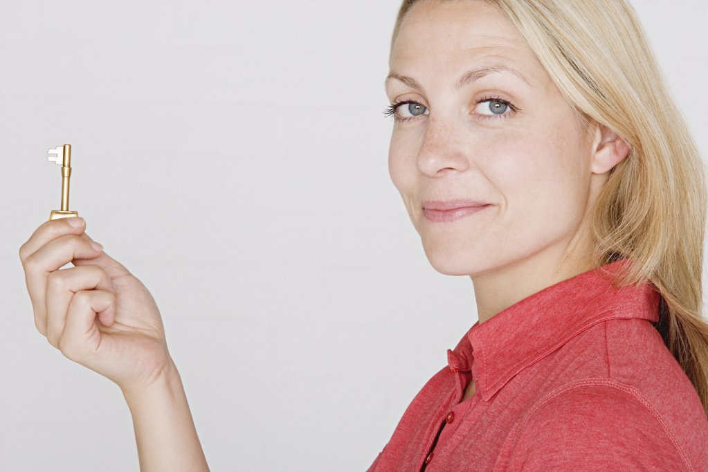 Stock Photo: 1439R-991017 Woman holding a key