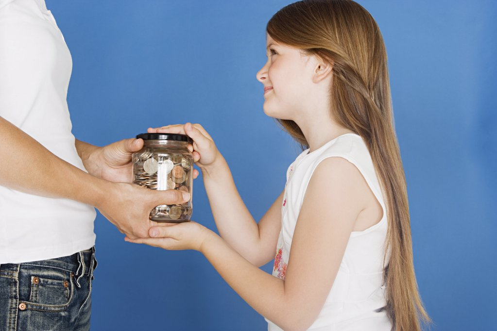Girl handing jar of coins to mother : Stock Photo