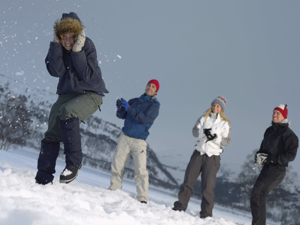 Stock Photo: 1439R-991847 Friends throwing snowballs