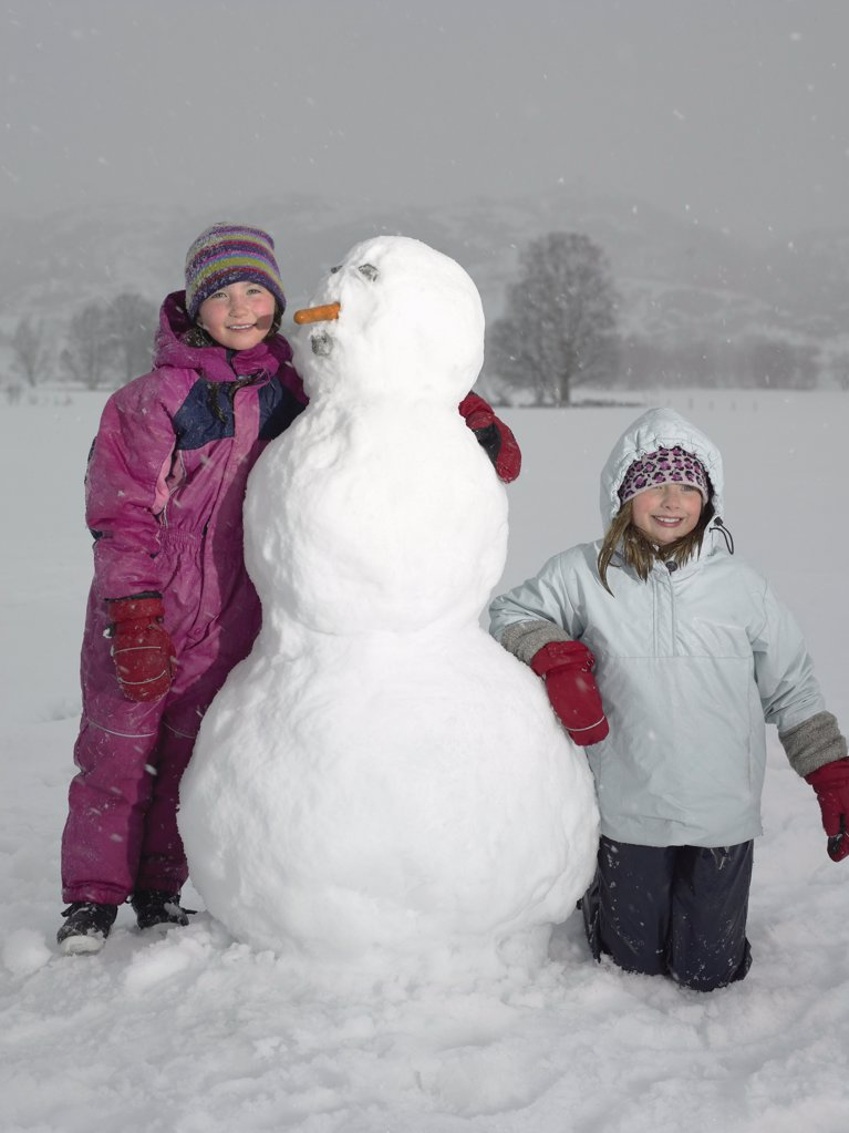 Stock Photo: 1439R-991859 Girls with snowman