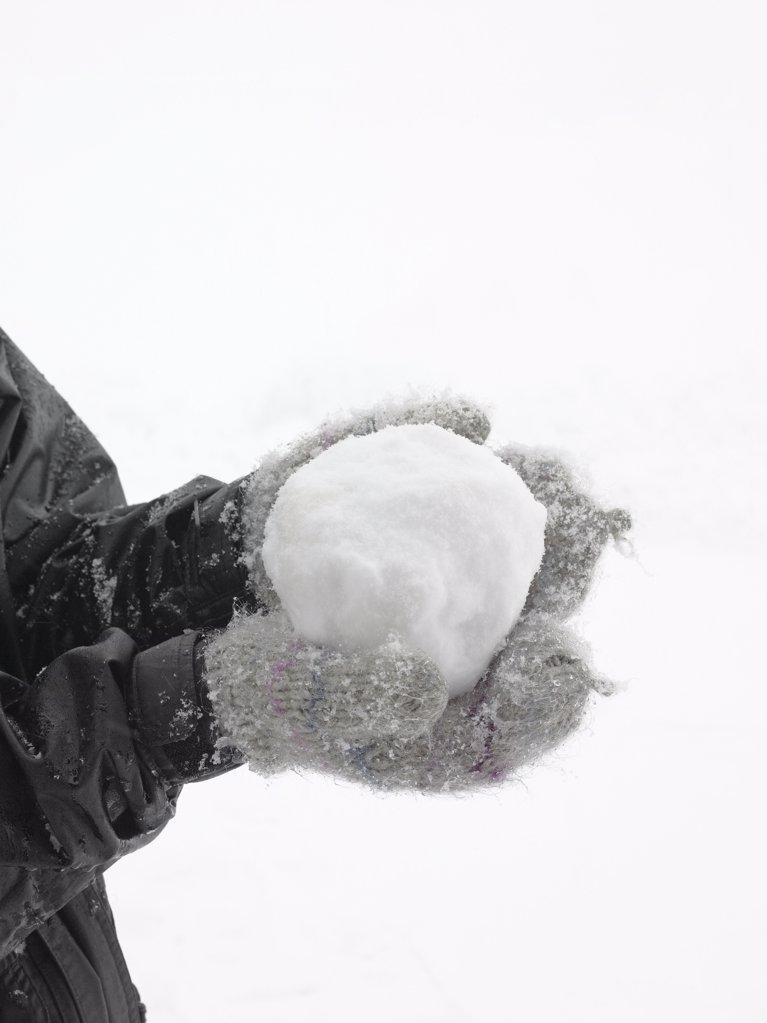 Stock Photo: 1439R-991880 Person holding a snowball
