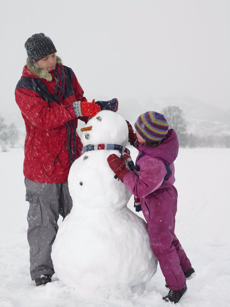 Father and daughter making a snowman : Stock Photo