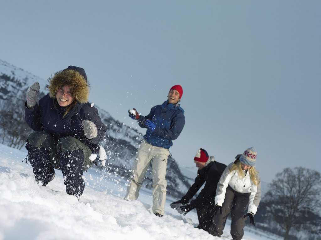 Stock Photo: 1439R-991934 Friends throwing snowballs