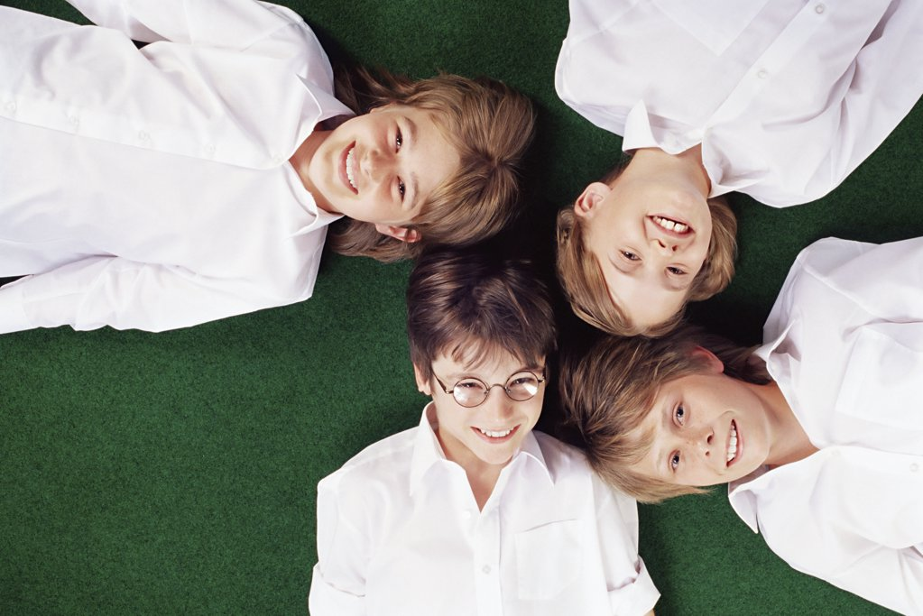 School friends lying on grass : Stock Photo
