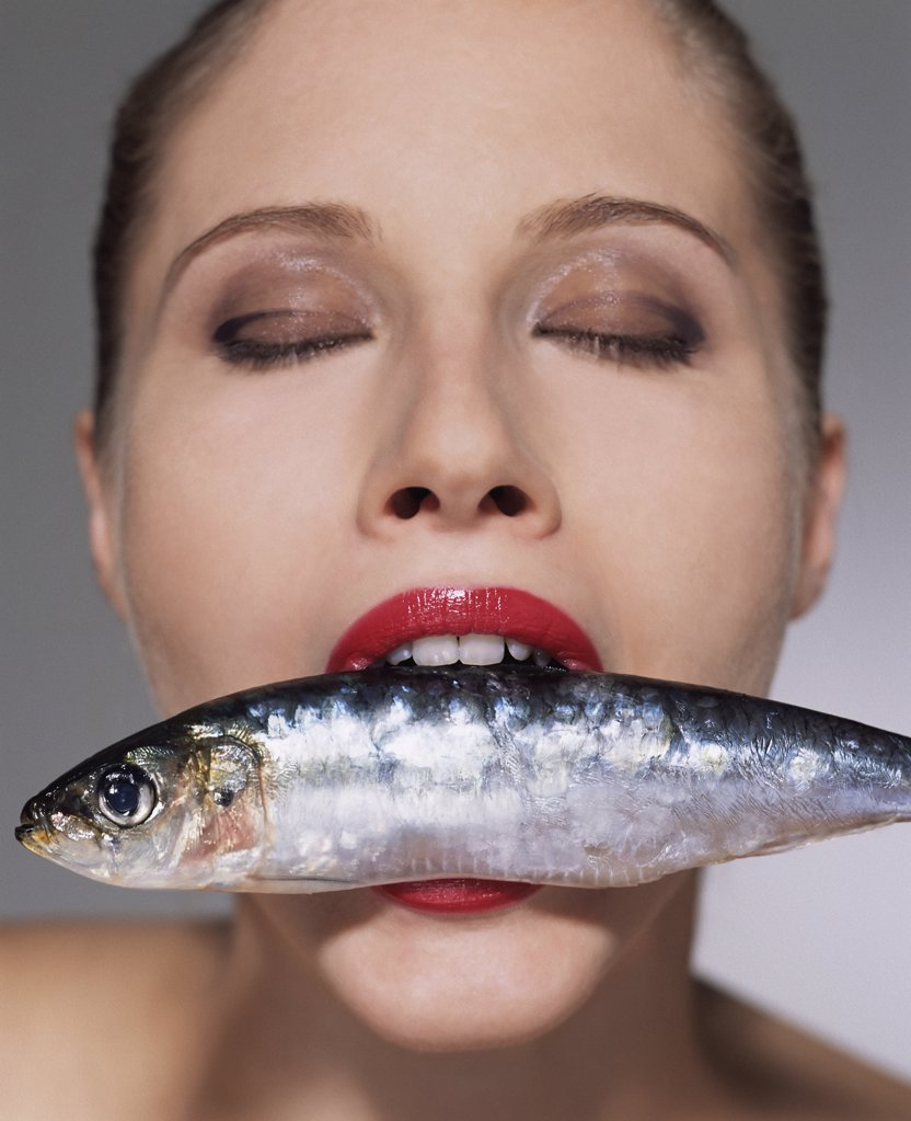 Woman with fish in her mouth : Stock Photo