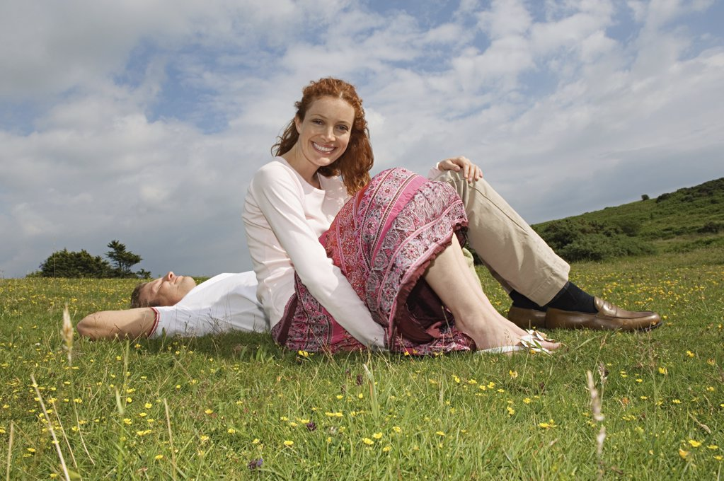 Couple resting in a field : Stock Photo