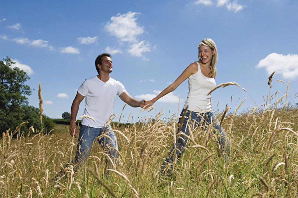 Stock Photo: 1439R-993292 Couple walking through field