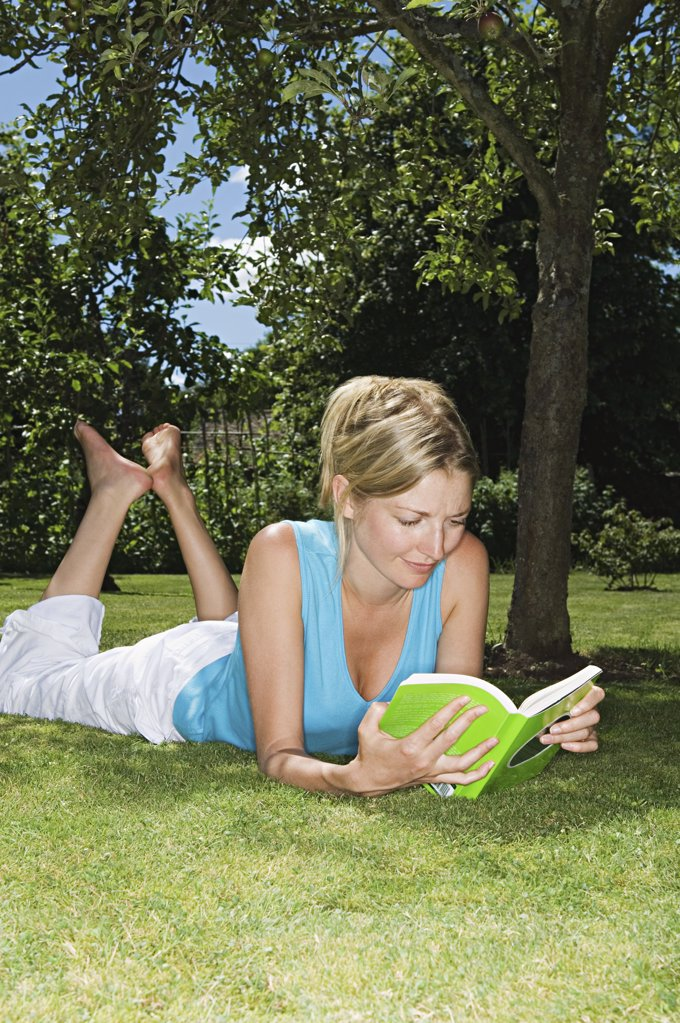 Stock Photo: 1439R-993324 Woman lying on grass reading a book