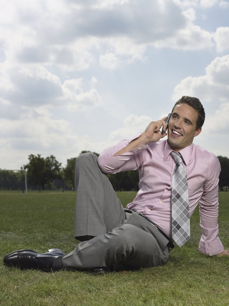 Stock Photo: 1439R-993922 Man using his cellular telephone in park