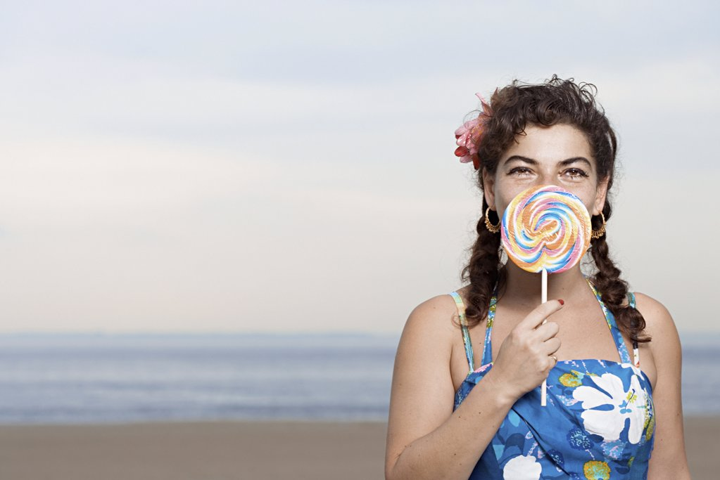 Stock Photo: 1439R-996009 Woman on beach with lollipop