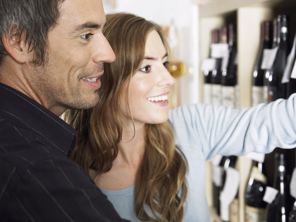 Couple looking at wine bottles : Stock Photo