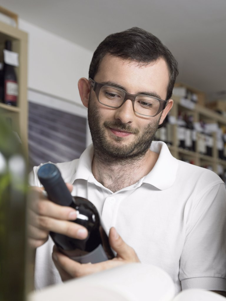 Stock Photo: 1439R-996129 Bearded and bespectacled man holding wine bottle