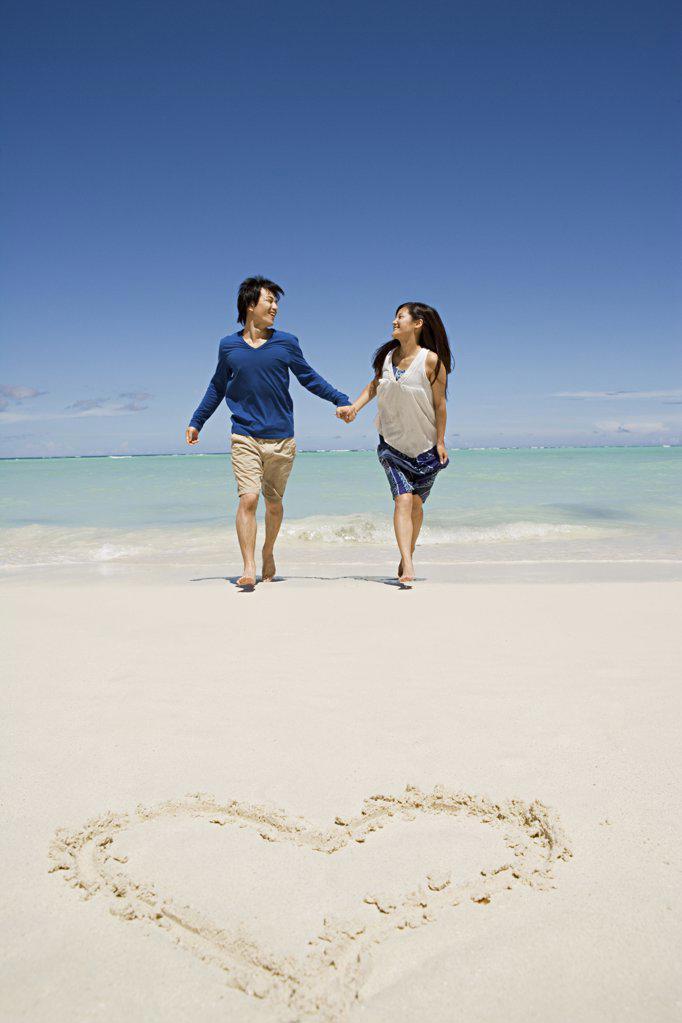 Newlyweds on beach near heart shape : Stock Photo