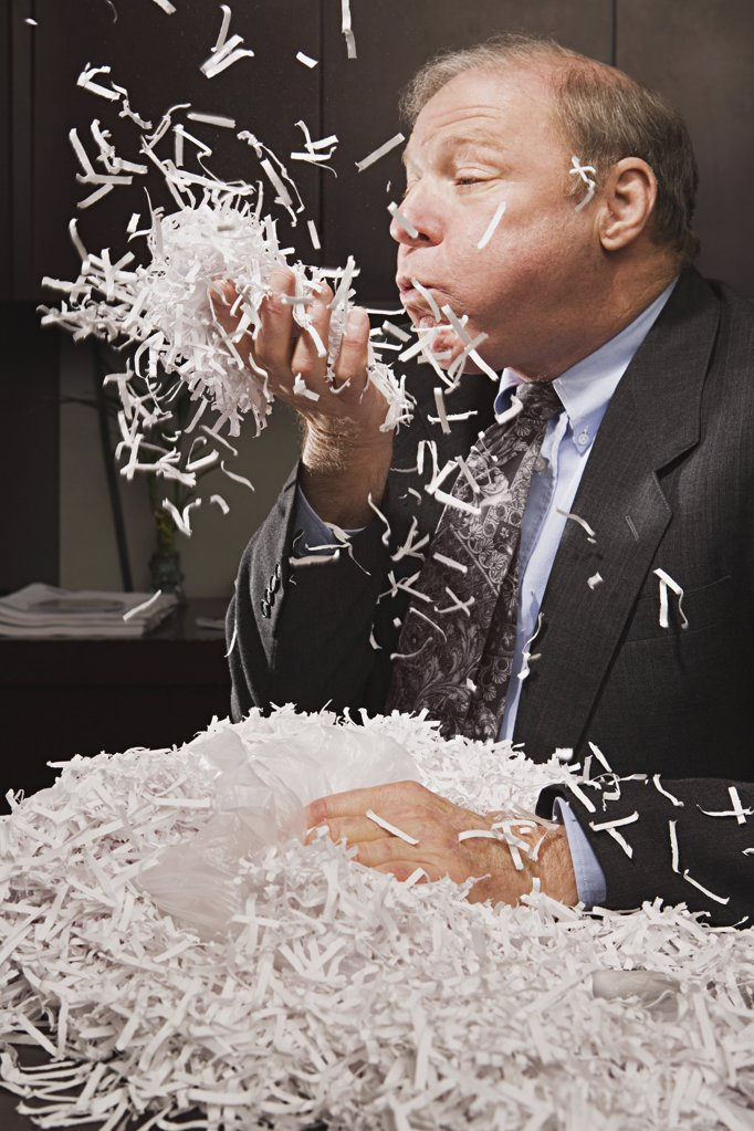 Mature businessman playing with paper shreddings : Stock Photo