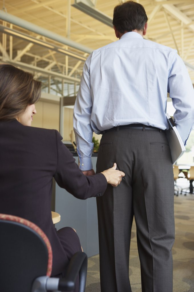 Businesswoman pinching colleagues buttock : Stock Photo