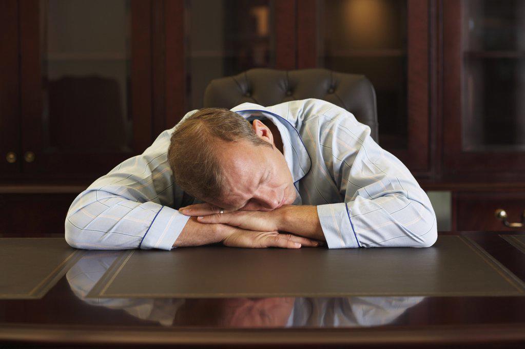 Businessman asleep at his desk : Stock Photo