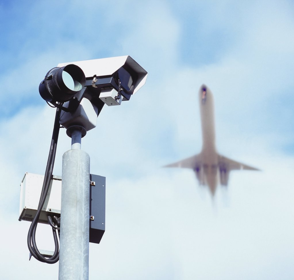 Aeroplane over surveillance camera : Stock Photo