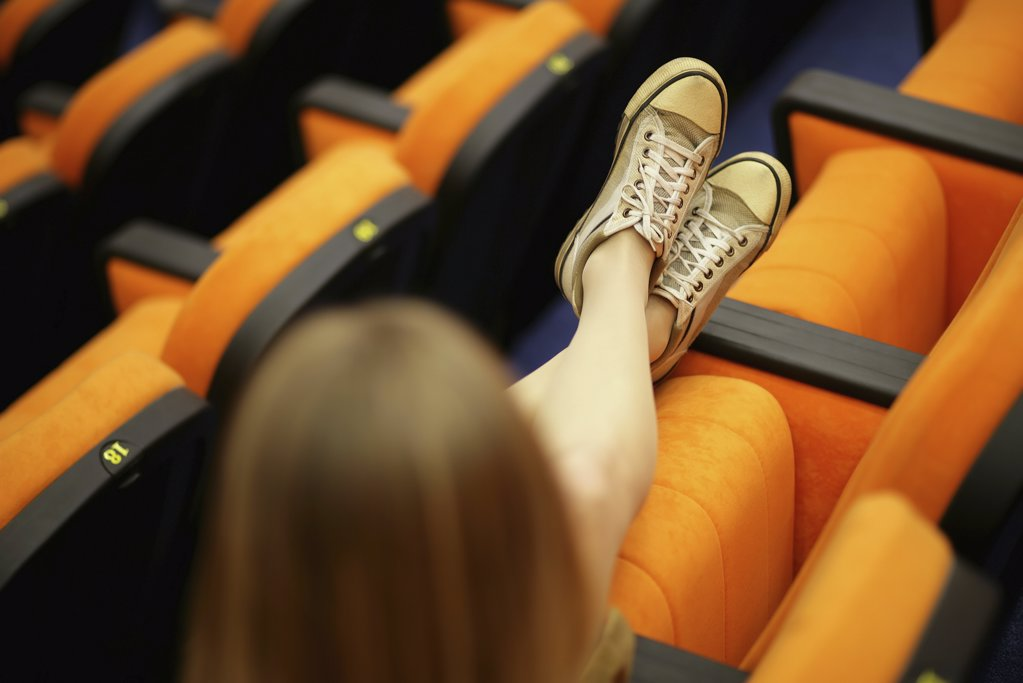 Woman stretching out her legs in lecture theatre : Stock Photo