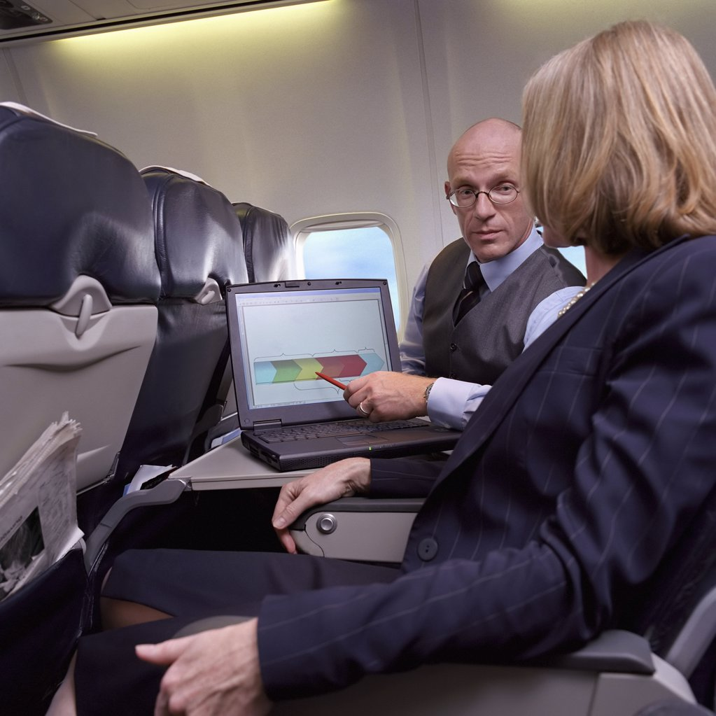 Stock Photo: 1439R-S010047 Business people using laptop on an aeroplane