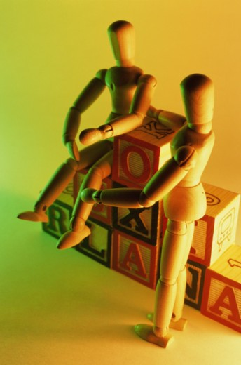 Close-up of wooden dolls on alphabet blocks : Stock Photo