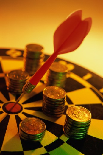 Stock Photo: 1441R-513 Stack of coins on a dartboard
