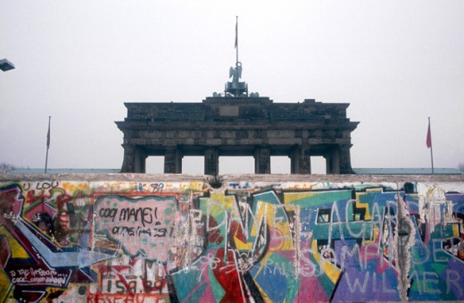 Graffiti on a wall with a memorial gate in background, Berlin Wall, Brandenburg Gate, Berlin, Germany : Stock Photo