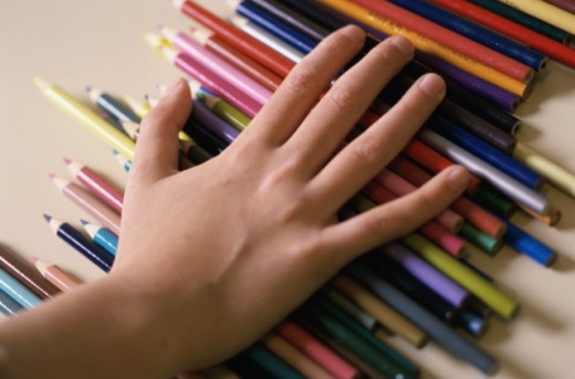 Stock Photo: 1445R-284 Close-up of a person's hand on colored pencils