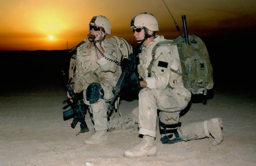 Two soldiers kneeling on the ground at dusk : Stock Photo