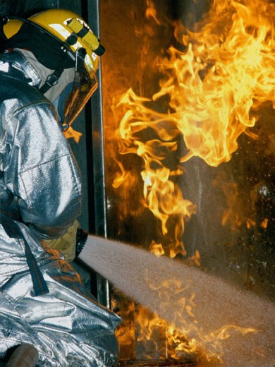Stock Photo: 1457-745 Rear view of a firefighter extinguishing a fire