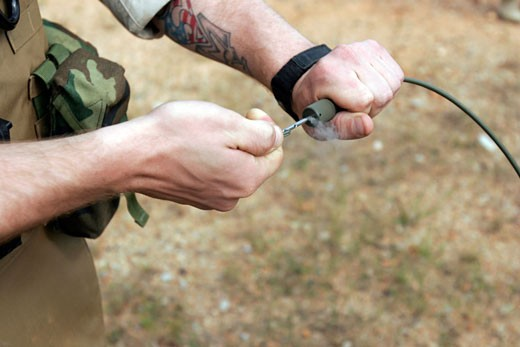 Stock Photo: 1457-997 Close-up of an Marine soldier pulling a detonation cord igniter to start a reaction detonating C-4 explosives