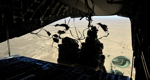 Container Delivery System bundles exit a C-17 Globemaster III during an airdrop mission. : Stock Photo