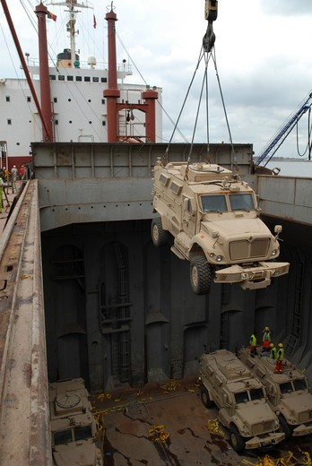 Stock Photo: 1457R-1380 A harbor crane lifts a mine-resistant, ambush-protected vehicle from the hull of a cargo vessel.