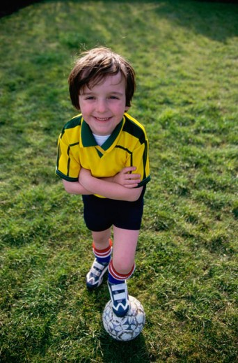Stock Photo: 1467-1067 High angle view of a boy standing with his foot on a soccer ball