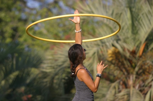 Stock Photo: 1467-1221 Sid profile of a young woman spinning a plastic hoop